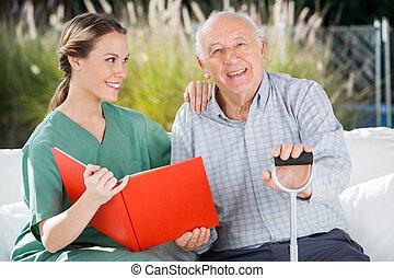 Happy Senior Man Sitting By Female Nurse Holding Book -...