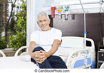 Happy Senior Man Sitting On Bed At Rehabilitation Center
