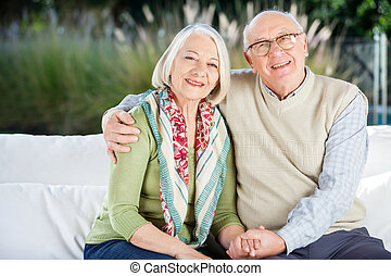 Happy Senior Man Sitting With Arm Around Woman On Couch -...