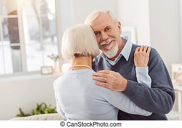 Happy senior man smiling while dancing with wife