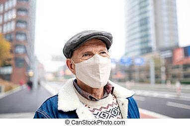 Happy senior man standing outdoors on street in city. Coronavirus concept.