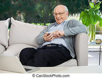 Happy Senior Man Text Messaging Through Smartphone At Porch