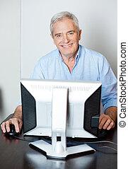 Happy Senior Man Using Computer In Class