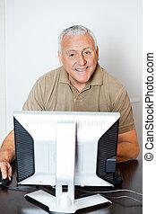 Happy Senior Man Using Computer In Classroom