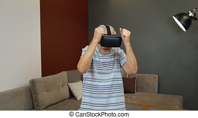 Happy senior man using virtual reality headset glasses. Elderly mature old grandfather rising his hand and trying to touch something, watching 3D video in 360 VR helmet. 6k downscale, slow motion