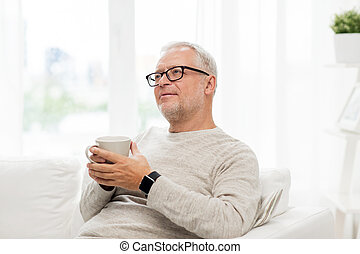 happy senior man with cup of tea at home