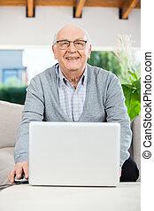 Happy Senior Man With Laptop At Nursing Home Porch
