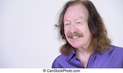 Studio shot of senior man with mustache wearing purple silky shirt against chroma key with white background