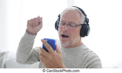 happy senior man with smartphone and headphones 122