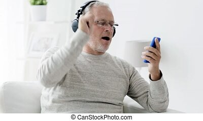 happy senior man with smartphone and headphones 92