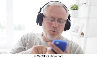 happy senior man with smartphone and headphones 123