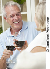 Happy Senior Man & Woman Couple Drinking Wine at Home
