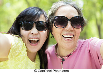happy senior mother and daughter taking selfie