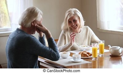 Happy senior older couple talking laughing having healthy morning breakfast