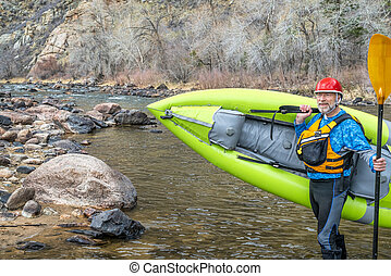 senior paddler carrying inflatable whitewater kayak - happy ...