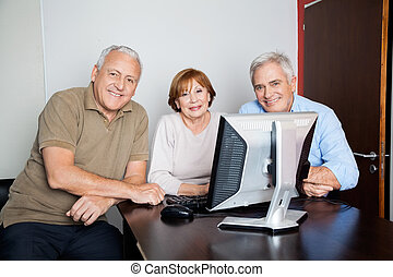 Happy Senior People Using Computer At Desk In Classroom
