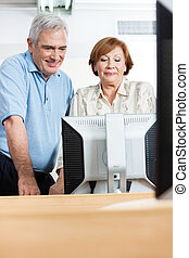 Happy Senior People Using Computer In Class