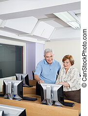 Happy Senior People Using Computer In Classroom