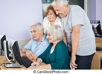 Happy Senior People Using Computer Together In Class