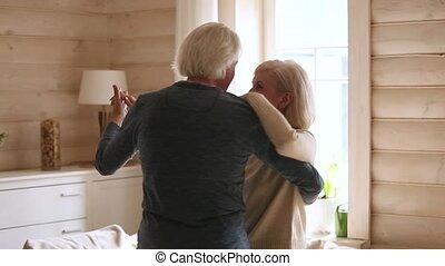 Happy senior romantic couple dancing in modern house living room