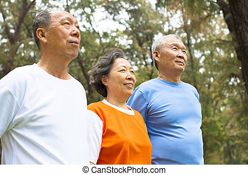 happy senior sibling standing a row in park