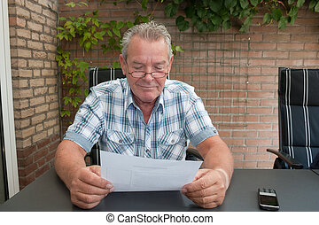 Senior smiling and reading a document