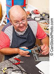 happy senior technician working in workshop