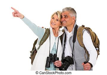 happy senior tourist pointing empty space on white background