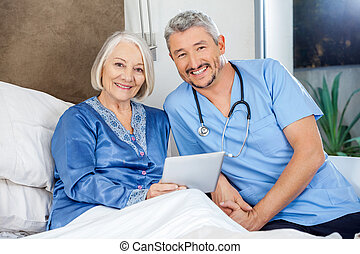 Happy Senior Woman And Caretaker With Tablet PC