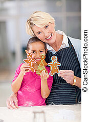 happy senior woman and granddaughter holding gingerbread cookies they just baked