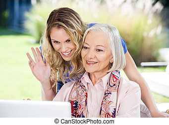 Happy Senior Woman And Granddaughter Video Chatting On Laptop