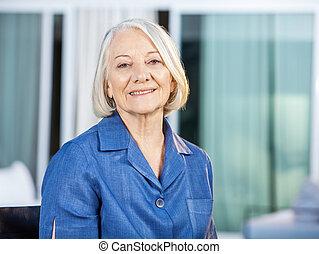 Happy Senior Woman At Nursing Home Yard