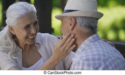 Happy senior woman cuddling with husband outdoors