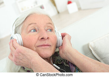 happy senior woman enjoying music with headphone at home