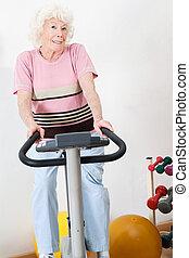 Happy Senior Woman Exercising On Bike