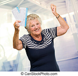 Happy Senior Woman Holding Boarding Pass, Indoors