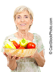 Happy senior woman holding vegetables