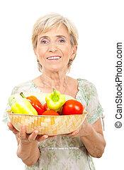 Happy senior woman holding vegetables