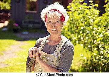 Happy senior woman in garden with shovel