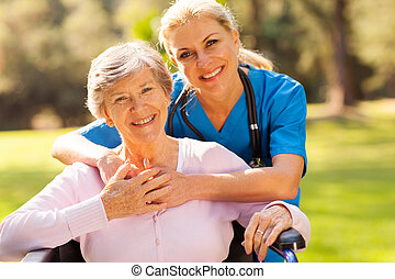 senior woman in wheelchair outdoors with caring caregiver