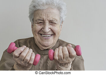 Happy senior woman is lifting the dumbbells