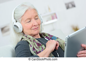 happy senior woman listening to music on digital tablet