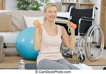 happy senior woman making fitness training with dumbbells at home