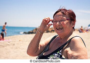 Happy senior woman on the beach