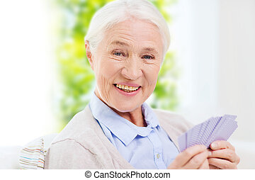 happy senior woman playing cards at home