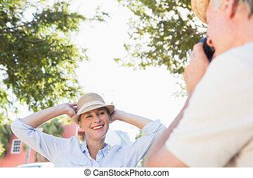 Happy senior woman posing for her partner taking photo