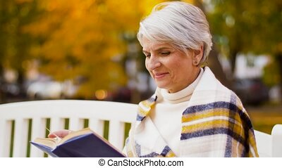 happy senior woman reading book at autumn park - old age,...