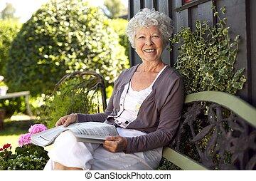 Happy senior woman reading newspaper in her backyard