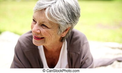 Happy senior woman relaxing in the park