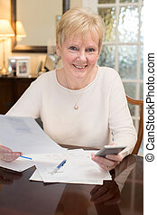 Happy Senior Woman Reviewing Domestic Finances At Home